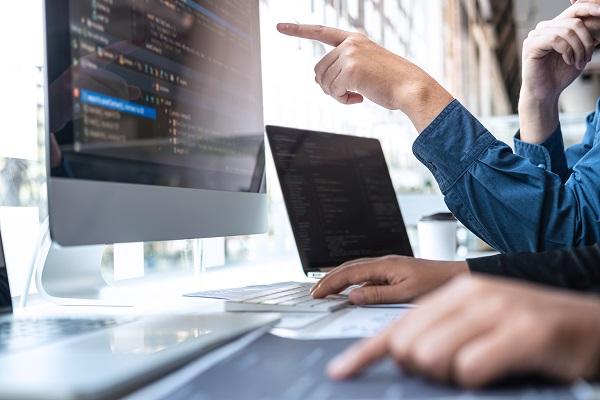Imagem com dois computadores e braços de duas pessoas, uma delas aponta para a tela e outra mexe no computador, o qual tem em sua tela códigos.