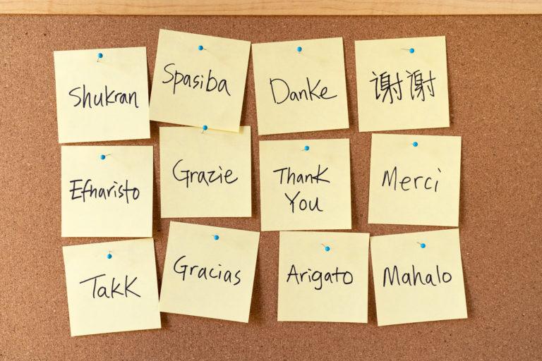 imagem ilustrativa com alguns stickers escritos obrigado em várias línguas.