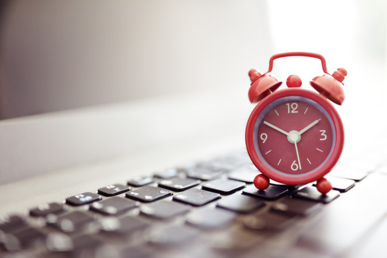 Despertador colocado sobre o teclado de um notebook.